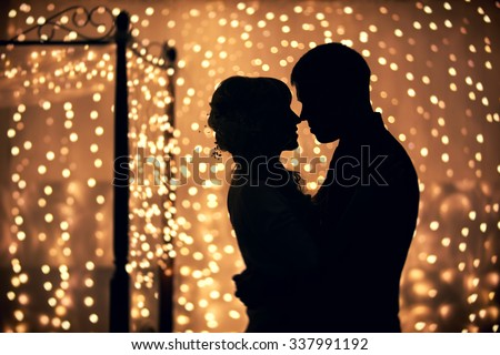 hugs lovers in silhouette against the background of garlands of lights - stock photo