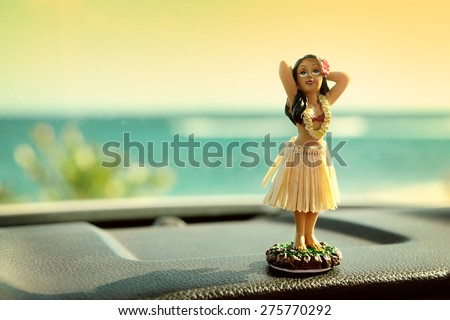 Hula dancer doll on Hawaii car road trip. Doll dancing on the dashboard in front of the ocean. Tourism and Hawaiian travel freedom concept. - stock photo