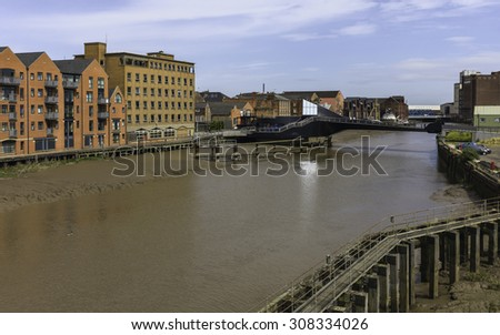 Hull, Humberside, UK. River Hull at low tide with view of Scale Lane swing bridge (closed), beached obsolete ship, and flanked by buildings near the estuary, Hull, Humberside, UK.
