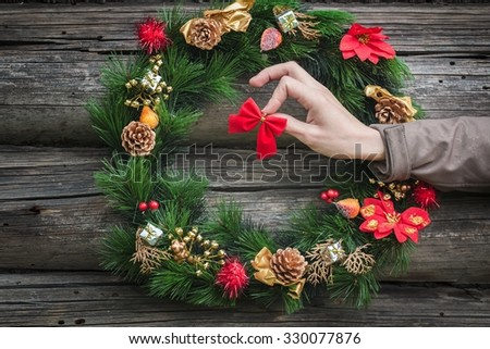 Human arm is hanging red bow on rustic log cabin wall with festive winter wreath - stock photo