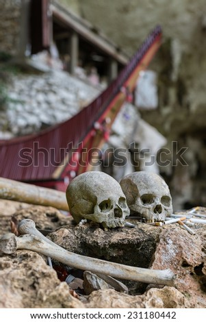 Human bones and skulls with cigarette offerings in Londa (Tana Toraja, South Sulawesi, Indonesia), traditional burial site with semi open coffins placed in caves or hanging from cliffs. - stock photo
