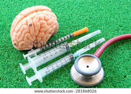 human brain and syringe on green grass background - stock photo