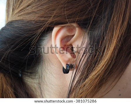 Human ear with mole and earring - stock photo