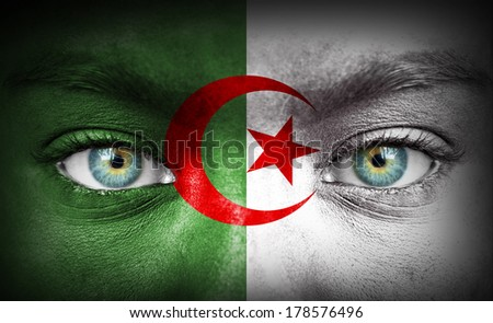 Human face painted with flag of Algeria - stock photo