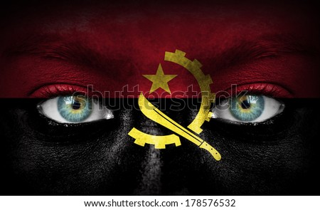 Human face painted with flag of Angola - stock photo