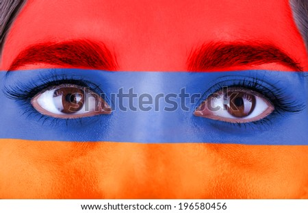 Human face painted with flag of Armenia - stock photo