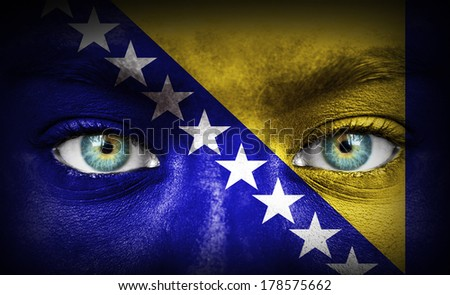 Human face painted with flag of Bosnia and Herzegovina - stock photo