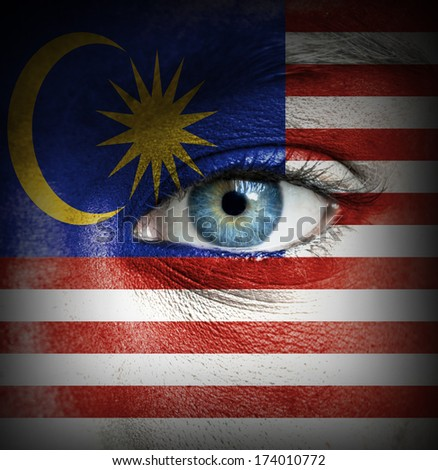 Human face painted with flag of Malaysia - stock photo