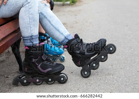 Human feet are wearing in-line skates. Woman and kid sitting on the bench while rollerblading