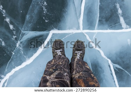Human feet in boots on the ice Baikal - stock photo
