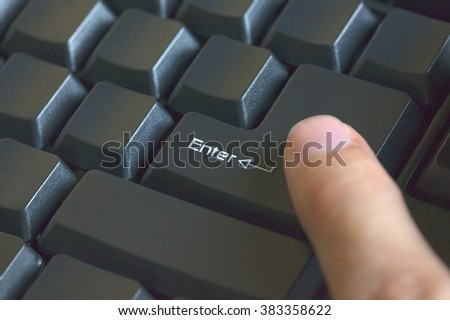 Human finger pressing enter keyboard (focus on enter key) - stock photo