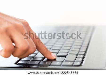 Human finger pressing on the enter key on laptop keyboard on white.