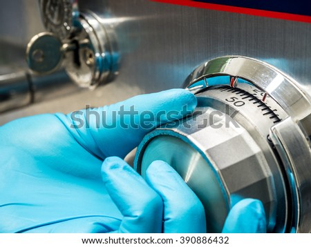 human fingers in glove turning the analog security password to open the steel save - stock photo