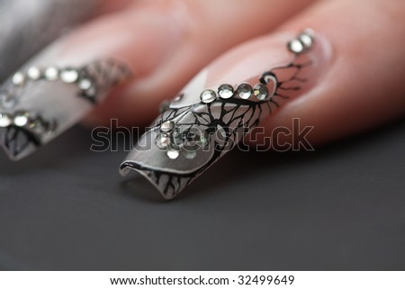 Human fingers with long fingernail and beautiful manicure over gray - stock photo