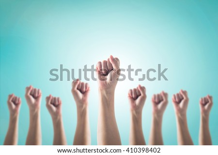 Human fist gesture among blur arm group on vintage blue sky background: Female woman clenched hand raising up showing power strong bunch of five: Women rights strengthening empowering conceptual idea