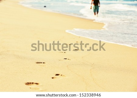 Human footprint in wet sand on the beach. - stock photo