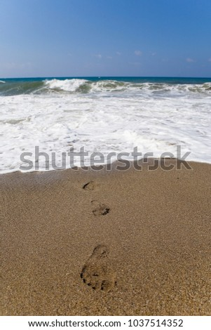 Human footprints lead from the raging sea. Water element.