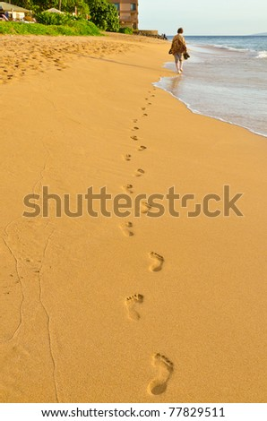 Human footprints leading away from the viewer - stock photo