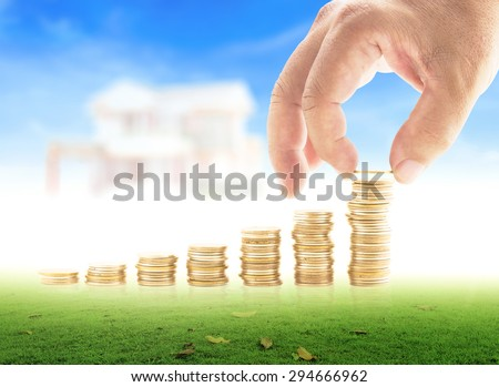 Human hand adding a golden coin in the final row of golden coins on meadow over blurred house on blue sky background. Concept for insurance, buying, renting, service, Saving, Future, Vision. - stock photo