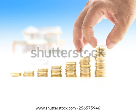 Human hand adding a golden coin in the final row of golden coins over blurred house and car on blue sky background. Concept for money coin, insurance, buying, renting, service. - stock photo