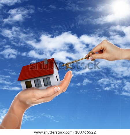 Human hand against blue sky background and house - stock photo