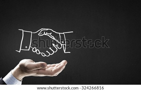 Human hand and sketch of handshake on gray background - stock photo