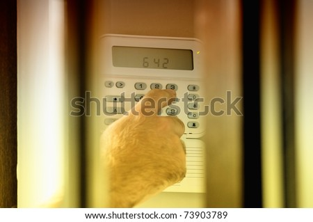 Human hand arming a burglar alarm system. The view is similar as a spy view this situation. - stock photo