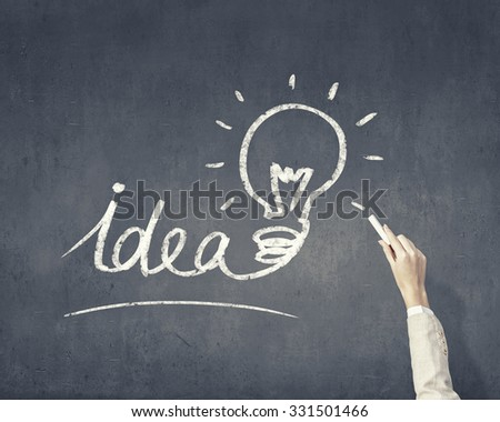 Human hand darwing light bulb as idea concept with chalk