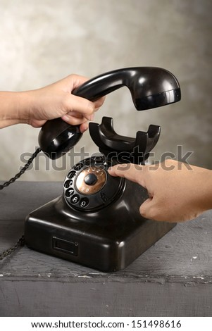 Human hand dialing numbers on antique telephone over abstract background - stock photo