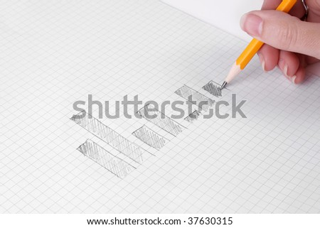 Human hand drawing business charts with a pencil on graph paper - stock photo