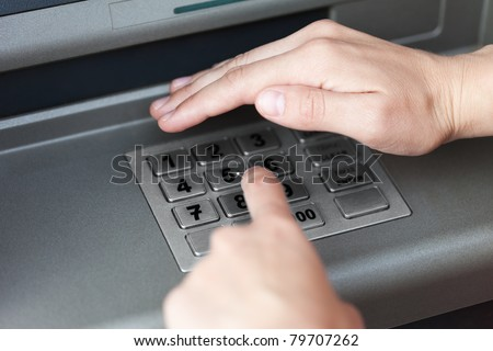 Human hand enter atm banking cash machine pin code - stock photo
