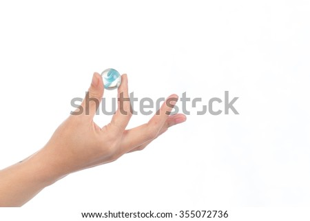 Human hand hold glass marbles balls on white blackground, selective focus - stock photo