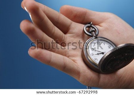Human hand holding a pocket watch.