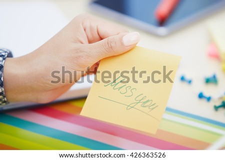 Human hand holding adhesive note with Miss you text