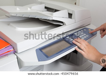 Human hand holding and start a purpose copier machine isolated on white background