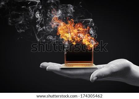 Human hand holding burning laptop on palm - stock photo