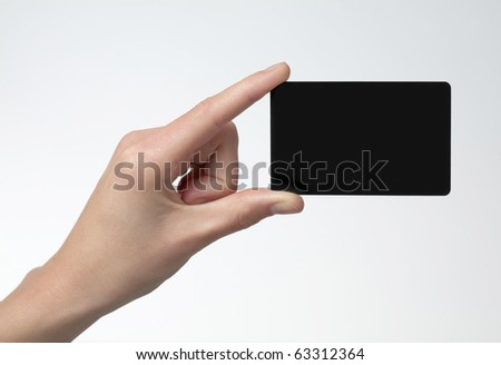 Human hand holding credit card with two fingers