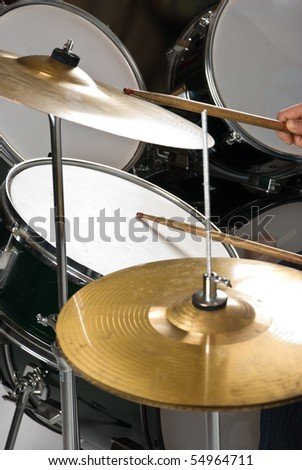 Human hand holding drumsticks playing drums and cymbal - stock photo
