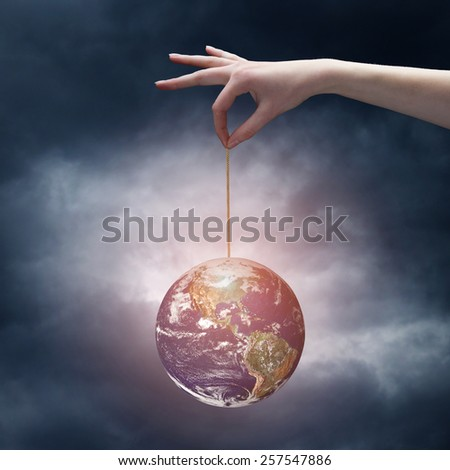 human hand holding Earth planet on rope. Elements of this image are furnished by NASA  - stock photo