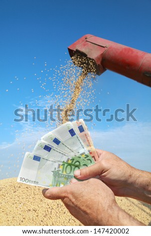Human hand holding Euro banknote with soy bean and combine in background