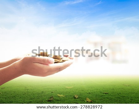 Human hand holding golden coins over blurred house on blue sky background. Concept for money coin, buying, renting, service, Investment, Insurance Agent, Saving, Planing, Building. - stock photo