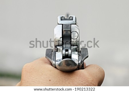 Human hand holding gun, hand aiming a handgun, .45 pistol. - stock photo