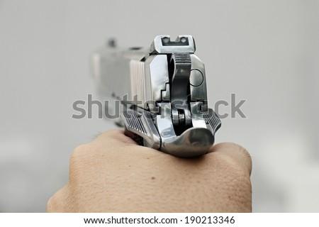 Human hand holding gun, hand aiming a handgun, .45 pistol. - stock photo