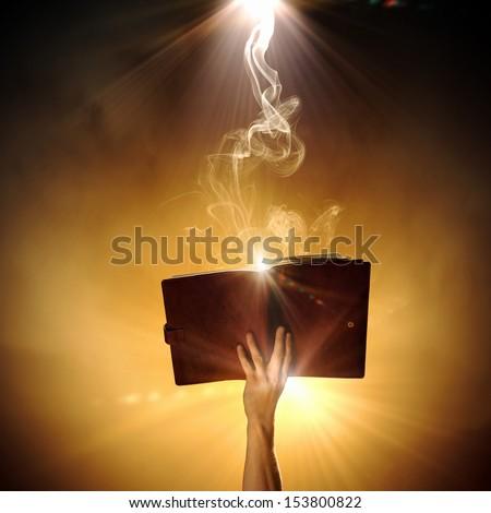 Human hand holding magic book with magic lights - stock photo