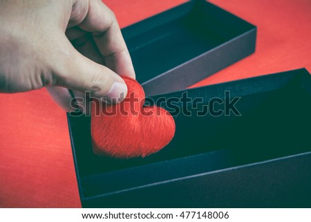 Human hand holding or putting a red heart-shaped in a black gift box for a Valentine's day, concept of care and love. Vintage tone effect and low key picture style.