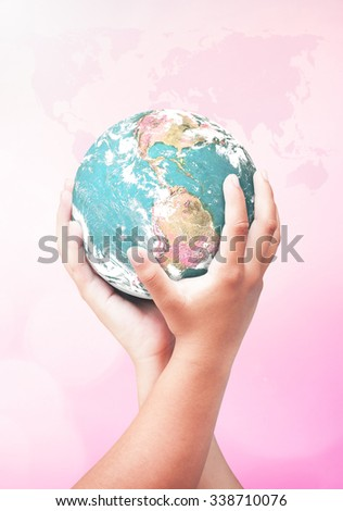 Human hand holding planet over blurred pink world map of clouds background. Investment, Synergies, Ecology, World Environment Day, CSR, Health Care concept. Elements of this image furnished by NASA. - stock photo