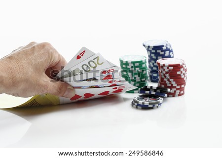 Human hand holding playing cards with gambling chips - stock photo