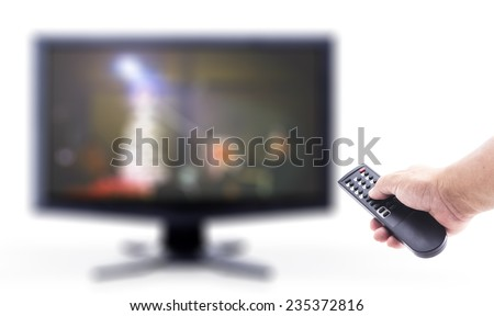 Human hand holding remote and out of focus TV LCD monitor isolated on white.