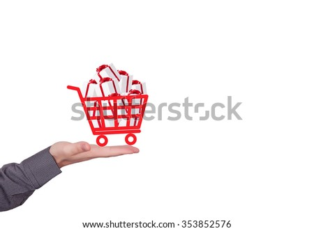 Human hand holding shopping cart full of gift boxes. Christmas time - stock photo