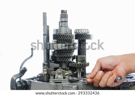 human hand holding spanner during gear box service on isolated background - stock photo